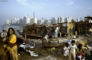 Shanty homes of fisher families and city immigrants on Back Bay, with tower blocks of Nariman Point in the background - Mumbai, India 2004. Credit: Paul Smith/Panos