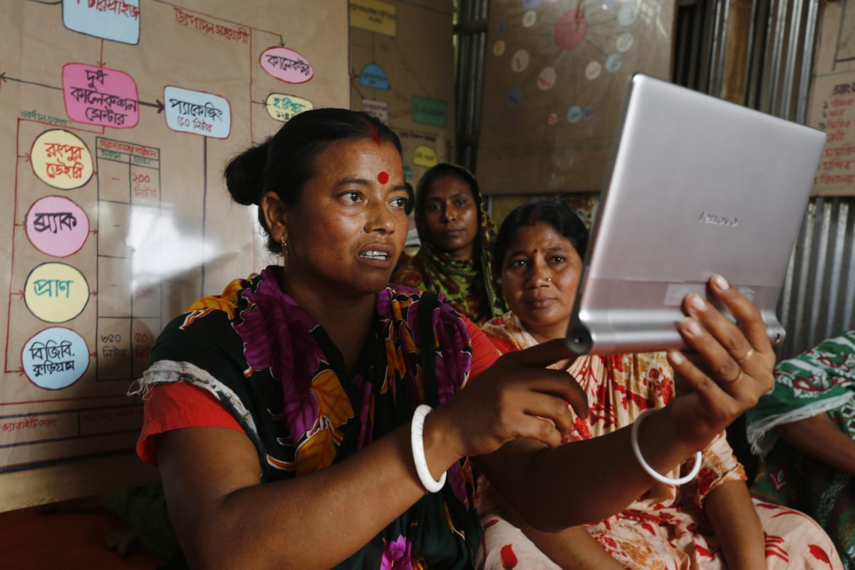 Renu Bala, President of Panjhorvanga Dairy Enterprise, Bangladesh, uses her tablet to communicate with buyers and collect market information. Credit: Abir Abdullah/Oxfam